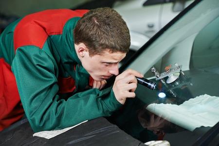 Automobile glazier repairman repairing windscreen or windshield of a car in auto service station garage photo