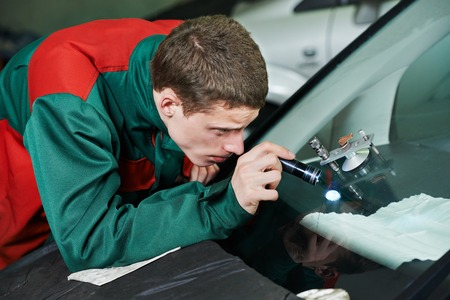 car glass: Automobile glazier repairman repairing windscreen or windshield of a car in auto service station garage