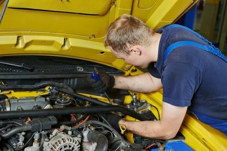 garage automobile: M�canicien automobile r�parateur serrer la vis avec une cl� lors de l'entretien de la voiture automobile � la r�paration du moteur station-service garage Banque d'images