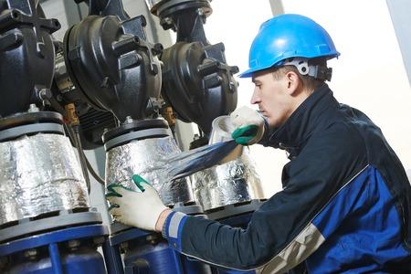 ingenieria industrial: trabajador de la construcci�n industrial en calderas tuber�a sala de trabajo de aislamiento t�rmico Foto de archivo