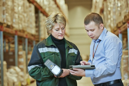 storage warehouse: manager and worker in warehouse with bar code scanner Stock Photo