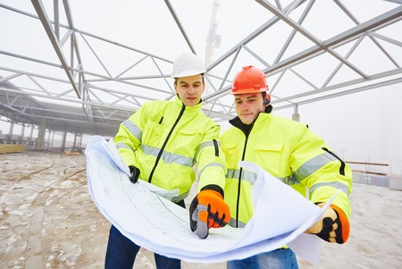 site manager: male engeneers construction foreman managers outdoors indoors at building site with blueprints