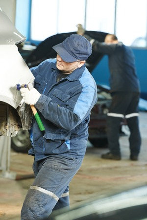 align: auto repair man worker flatten and align metal body car with hammer in automotive industry