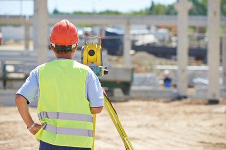 tachymeter: Portrait of builder worker with theodolite transit equipment at construction site outdoors during surveyor work