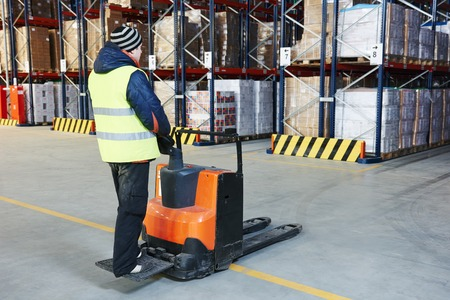 stockpile: Electric forklift pallet stacker truck equipment at work in warehouse