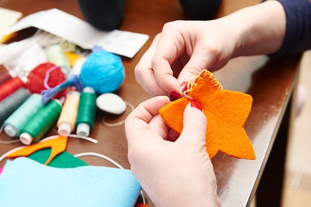 xmas crafts: Process of hand made soft toys sewing with felt and needle for Christmas tree decoration Stock Photo