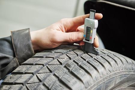 Auto Service man werknemer het meten van rubber auto wiel band beschermer Stockfoto
