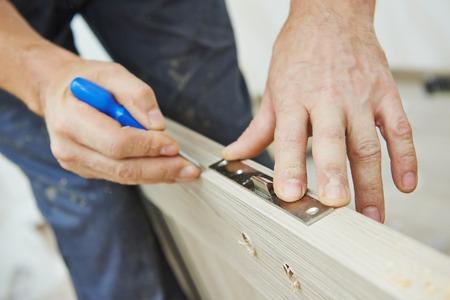 Close-up carpenter hands with doorlock during lock process installation into wood door Standard-Bild