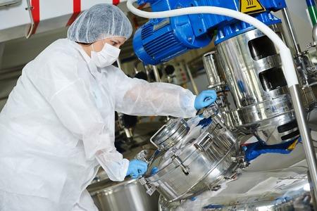 trabajador farmacéutica con el equipo de tanque de mezcla en la línea de producción en la farmacia fábrica fabricación industria