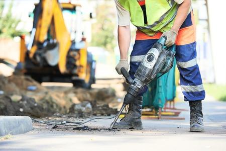 equipo: Trabajador del constructor con neumático equipo de perforación de martillo rompiendo el asfalto en el sitio de construcción de carreteras