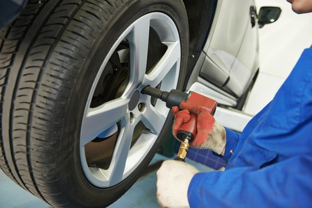 pneumatic tyres: car mechanic screwing or unscrewing car wheel of lifted automobile at repair service station