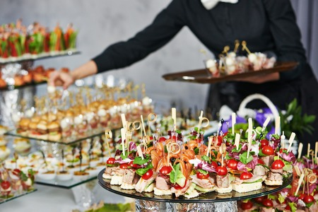 Waiter with meat dish serving catering table with food snacks Foto de archivo