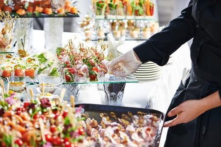 negocios comida: Camarero con plato de carne que sirve de mesa de catering con bocaditos de comida Foto de archivo