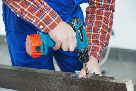 carpenter at interior wood door lock installation working with drill photo