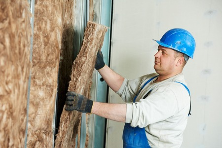 erector: cheerful plasterer worker at a indoors wall insulation works
