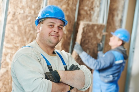 foremaster: cheerful plasterer worker at a indoors wall insulation works
