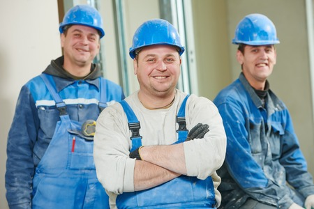 erector: cheerful plasterboard workers team at a indoors wall insulation works