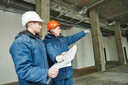 real leader: young male engeneers workers foreman at a indoors building site with blueprints Stock Photo