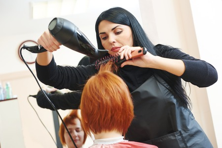 blow dryer: hairdresser drying hair with blow dryer of woman client at beauty parlour after highlighting Stock Photo