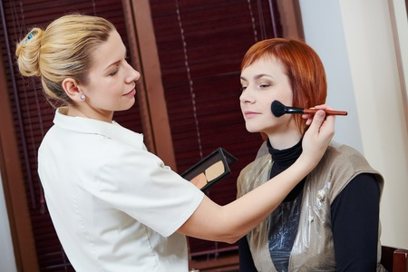 tonal: Makeup artist with paintbrush applying tonal cream to female client in beauty salon