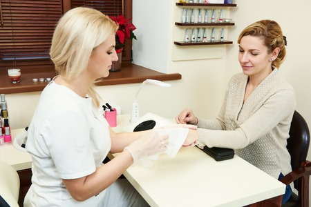 Manicurist with client perfoming hand nail protection and care in beauty salon photo