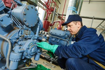 maintenance: service engineer worker at industrial compressor refrigeration station repairing and adjusting equipment at manufacturing factory Stock Photo