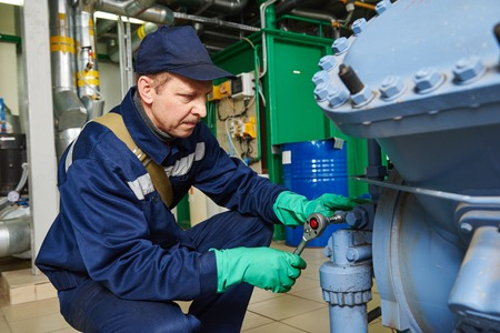 service engineer worker at industrial compressor refrigeration station repairing and adjusting equipment at manufacturing factory Archivio Fotografico