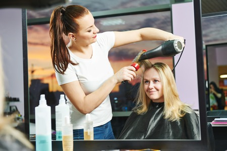 hairdresser drying hair with blow dryer of woman client at beauty parlour after highlighting photo