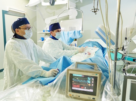 cardiosurgery: Team of vascular surgeon in uniform perform operation on a patient at cardiac surgery clinic