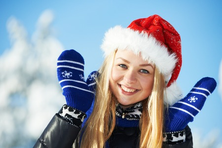 warm clothing: happy young smiling woman with red hat in warm clothing at winter snow outdoors Stock Photo