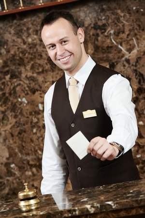 an attendant: smiling male receptionist passing key card to guest