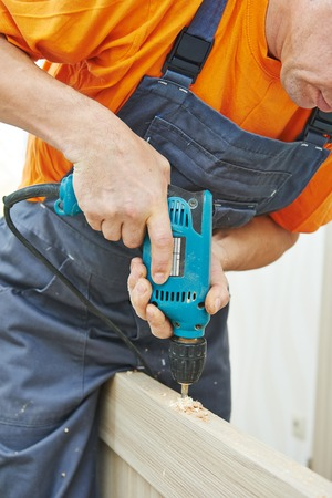 doorlock: carpenter at interior wood door lock installation working with drill Stock Photo