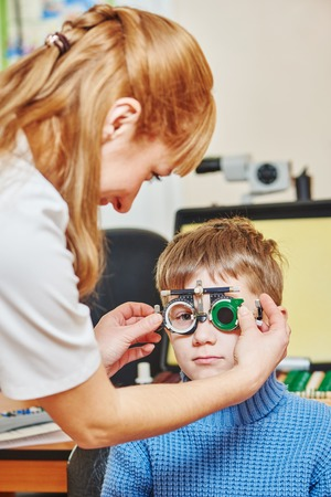 doctor of optometry: Optometry concept. female doctor ophthalmologist or optometrist helps young boy with phoropter during sight testing or eye examinations in clinic