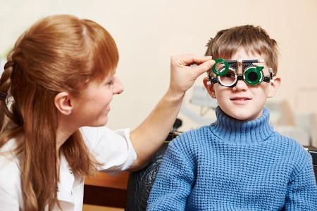 oculista: Concepto de la optometría. médico oftalmólogo u optometrista femenina ayuda muchacho joven con phoropter durante las pruebas o exámenes de los ojos a la vista en la clínica