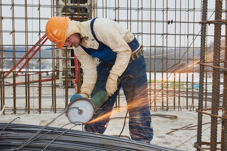 mounter: Construction builder worker with grinder machine cutting metal reinforcement rebar rods at building site