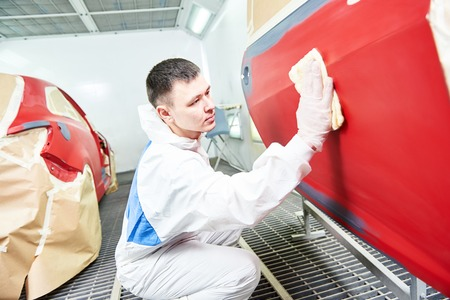 priming: auto mechanic worker painting a red car in a paint chamber during repair work