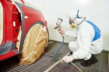 Mécanicien automobile travailleur peindre une voiture rouge dans une chambre de peinture lors de travaux de réparation Banque d'images - 36780068