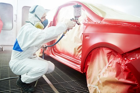 auto garage: auto mechanic worker painting a red car in a paint chamber during repair work