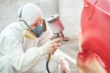 painters: auto mechanic worker painting a red car in a paint chamber during repair work