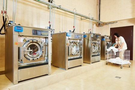 lavanderia: servicios de limpieza. Mujer de carga máquina lavadora de ropa con tela
