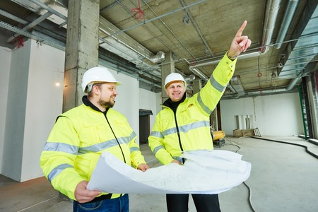 jobsite: young male engeneers workers foreman at a indoors building site with blueprints Stock Photo
