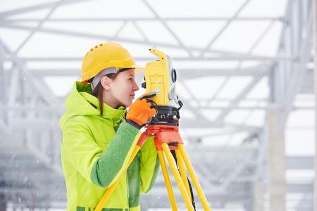 herramientas de construccion: trabajador agrimensor femenino que trabaja con equipos de tr�nsito teodolito en el sitio de construcci�n de la carretera al aire libre