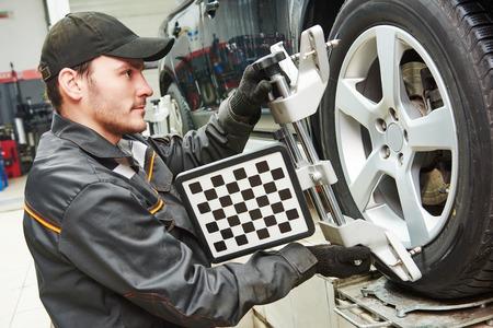автомеханик установка датчика во время регулировки подвески и автомобильной установки колес работы при ремонте станции технического обслуживания Фото со стока