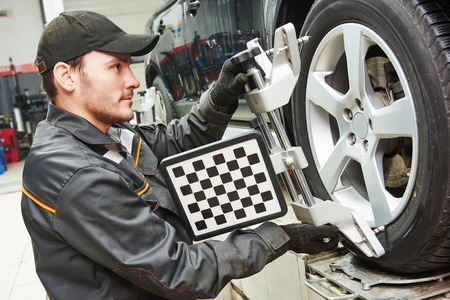 alignment: car mechanic installing sensor during suspension adjustment and automobile wheel alignment work at repair service station