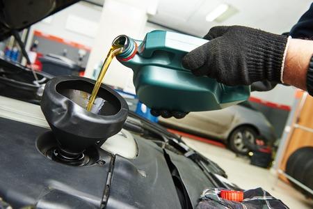 trabajador petroleros: t�cnico mec�nico de autom�viles sustituci�n y verter el aceite de motor en el motor del autom�vil al mantenimiento de la estaci�n de servicio de reparaci�n Foto de archivo