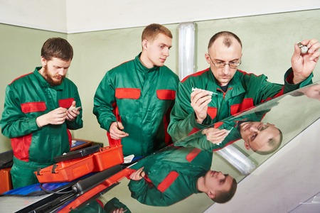 teaching stations: Automobile glazier repairman at windscreen repair of a car in auto service station garage Stock Photo