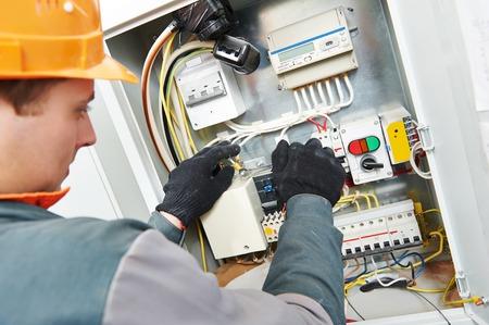 electricidad industrial: Adultos jóvenes de electricista ingeniero constructor de equipos atornillar la caja de fusibles