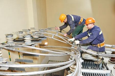 Electricians lineman repairman worker or installers at huge power industrial transformer installation work