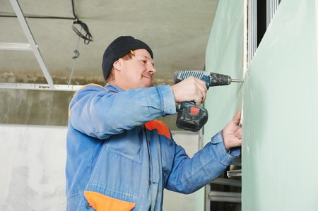 mounter: Carpenter joiner plasterer with screwdriver mounting gypsum plasterboard system at toilet