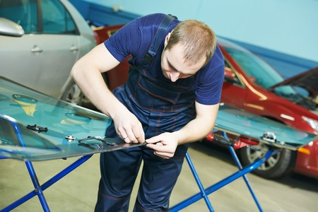 glasscutter: Automobile glazier works with windscreen or windshield of a car in auto service station garage before installation